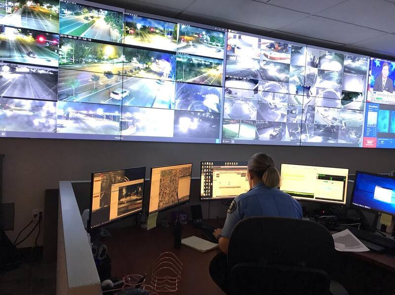 A police analyst sits at a workstation in front of a wall of video monitors.